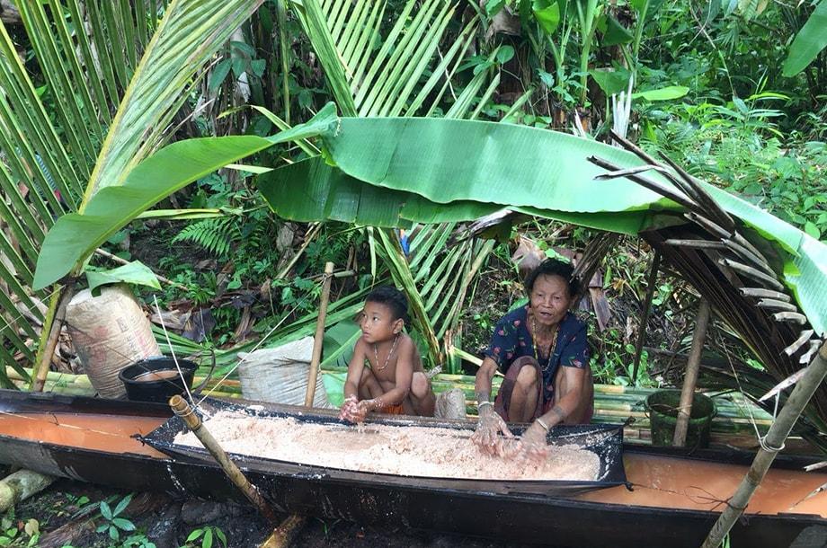 Femme Mentawai et son enfant préparant le sagou