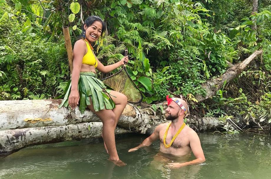 Femme assise sur un tronc et homme dans une rivière