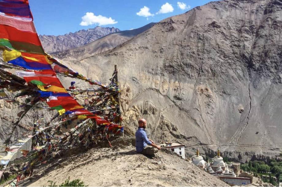 Montagnes Ladakh drapeaux tibétains homme meditation