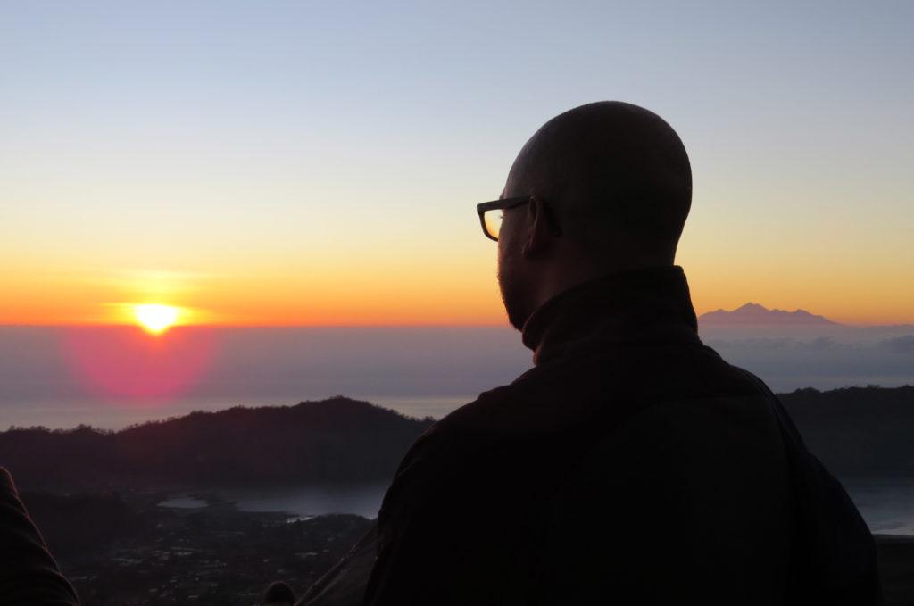 quel voyageur de dos regarde soleil levant sur mont Batur Bali Indonésie