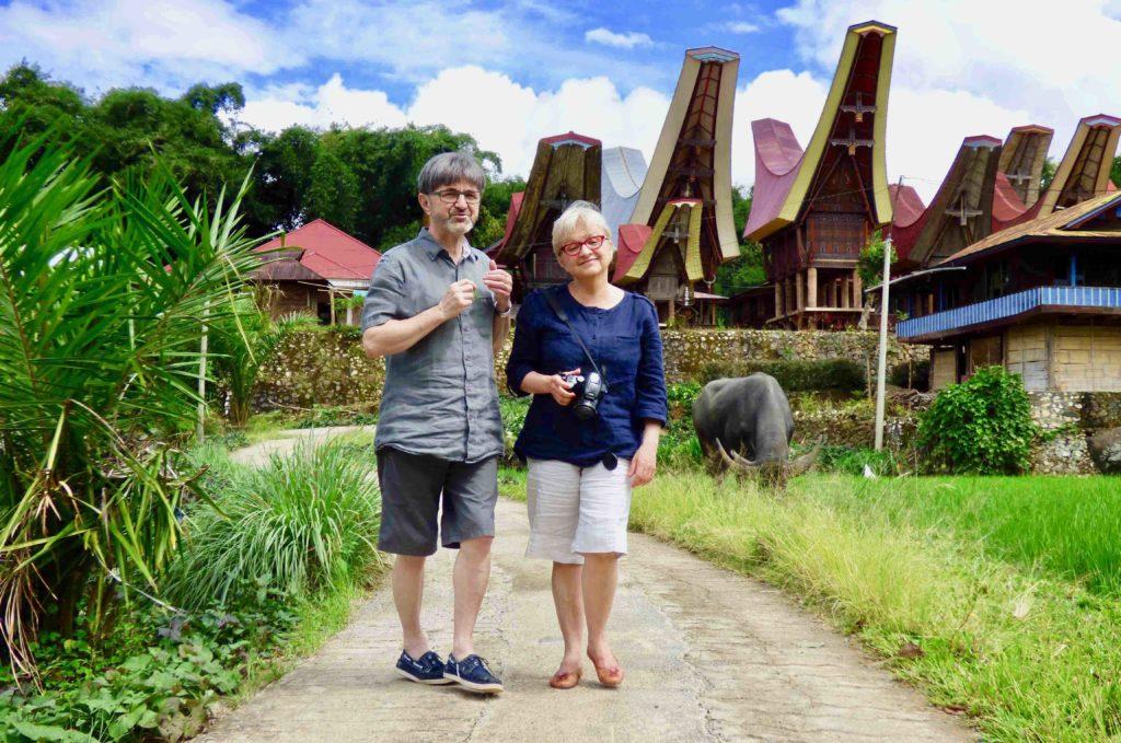 Un homme et une femme voyageur devant Tongkonan voyage Indonésie