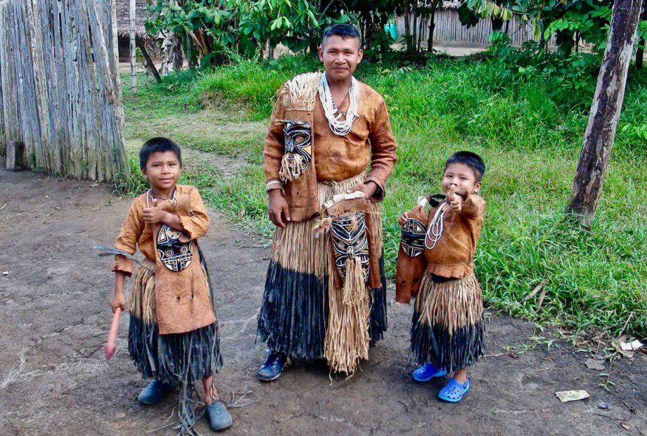 un homme et deux enfants indiens d'Amazonie en tenue traditionnelle
