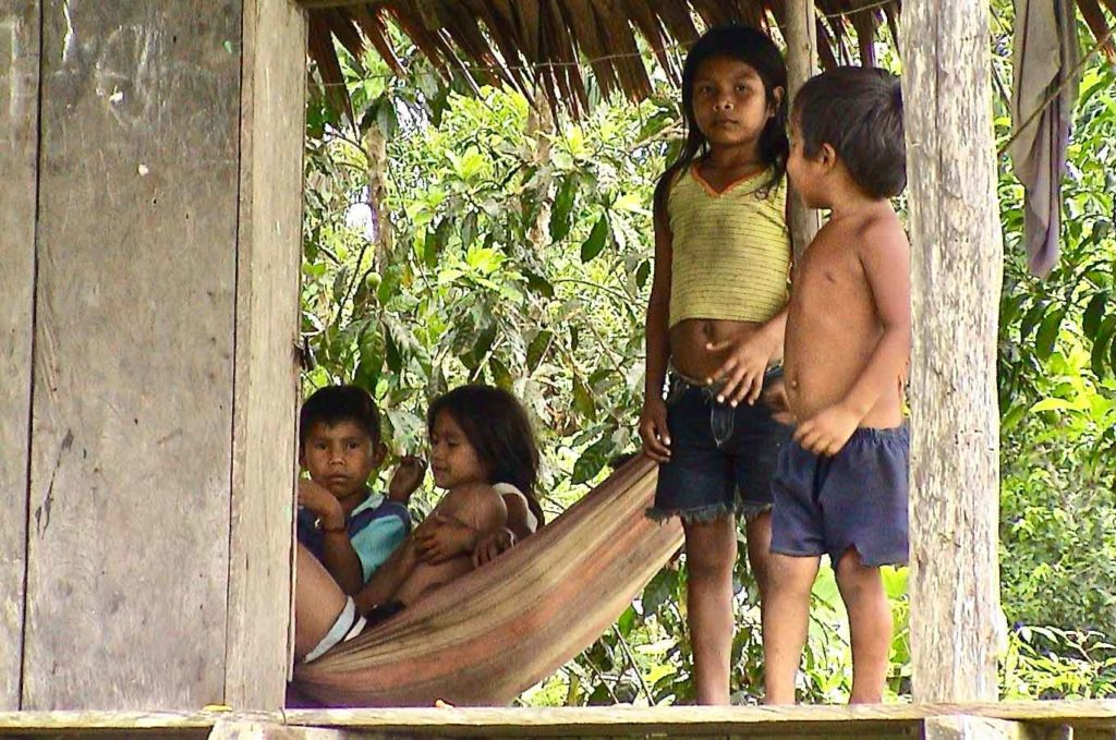 Groupe d'enfants deux enfants debout et deux dans un hamac Indiens d'Amazonie Yucuna