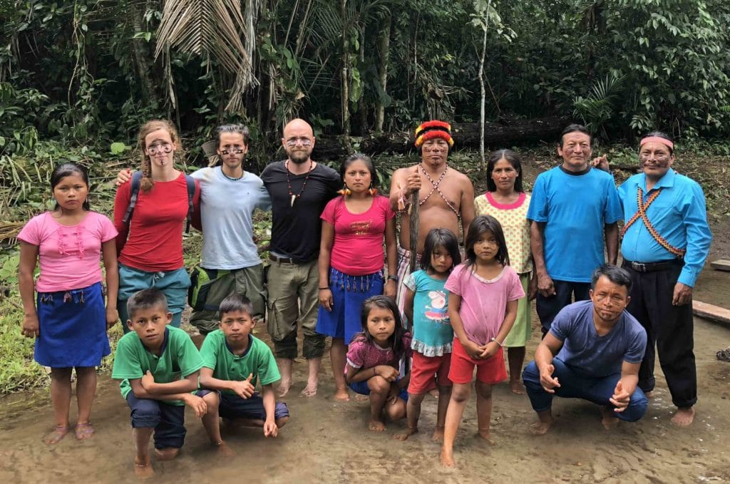Groupe d'Achuar et voyageurs les pieds dans la rivière dans la foret amazonienne en voyage en Équateur