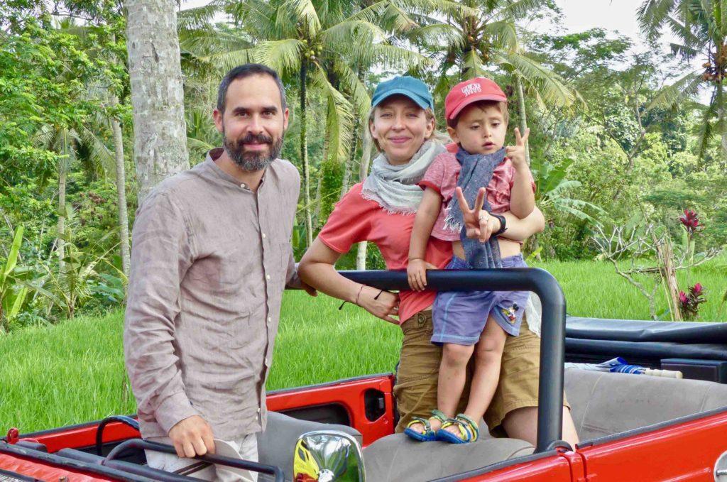 Famille avec jeune enfant dans une voiture vintage devant rizières et cocotiers en Indonésie