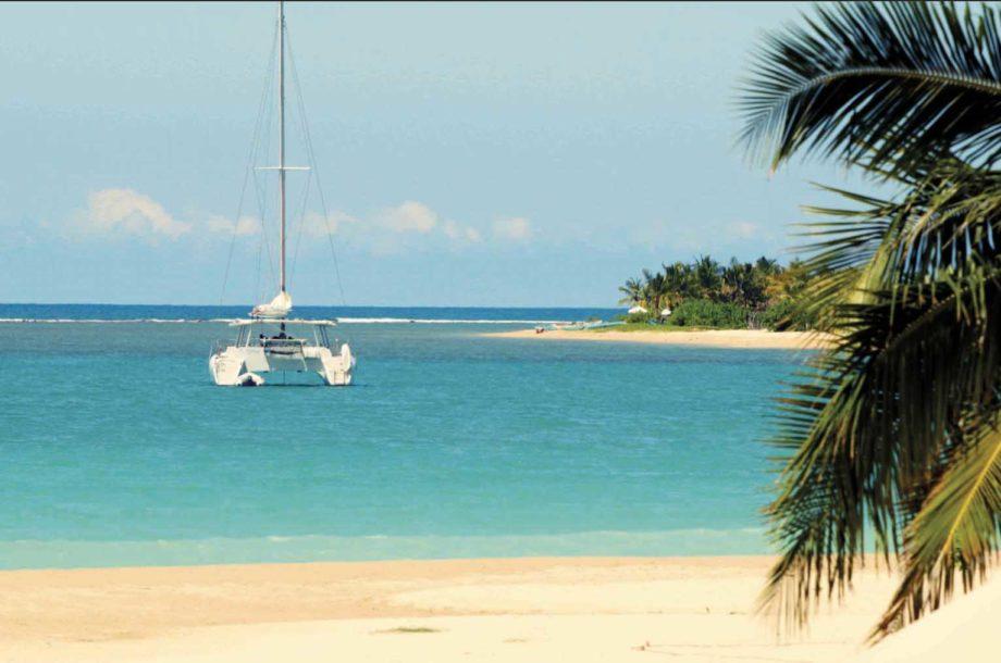 catamaran sur une mer bleue devant plage de sable au Sri Lanka